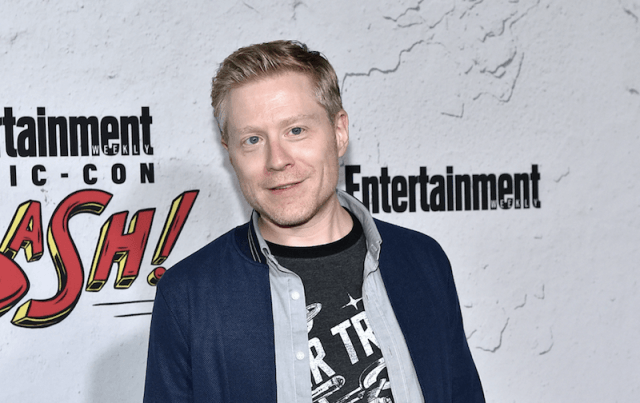 Anthony Rapp smiling and standing on a red carpet.
