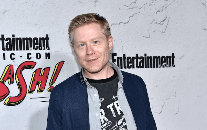 Anthony Rapp smiling and standing at a premiere