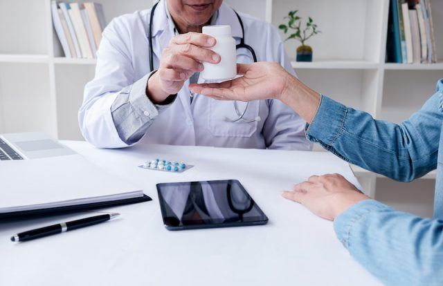 A doctor handing a patient a white bottle of pills.