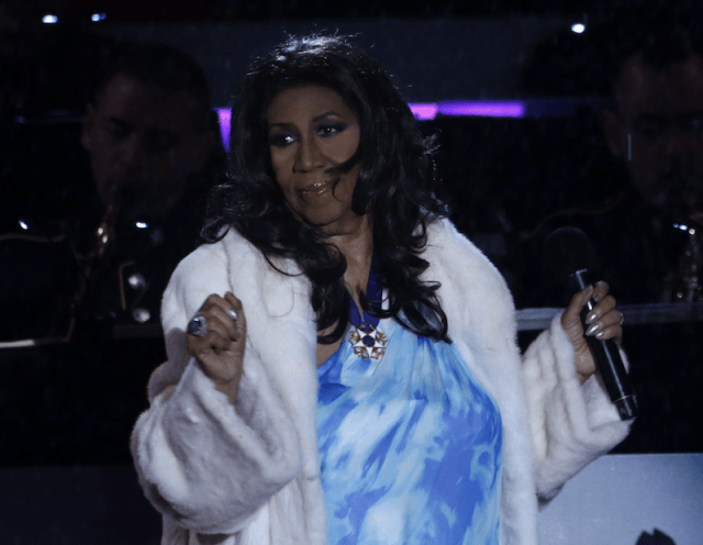 Aretha Franklin performing on stage.