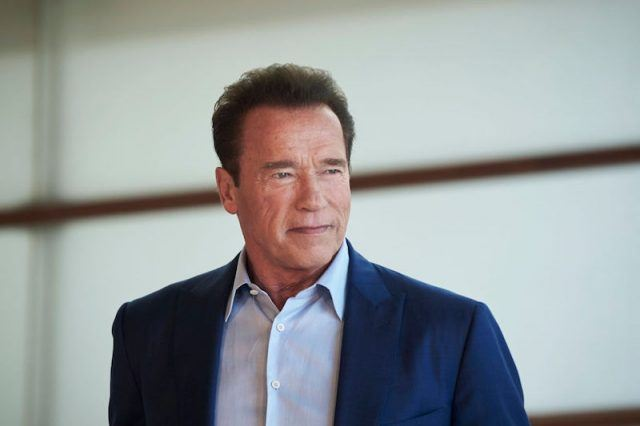 Arnold Schwarzeneggar stands in a blue blazer as he looks towards the side.