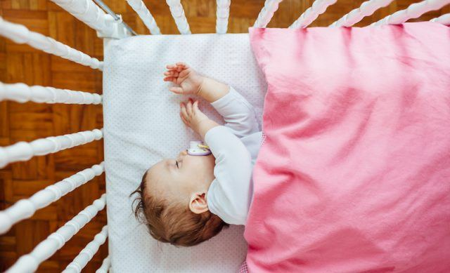 A baby sleeps soundly in a white crib with a pink blanket.