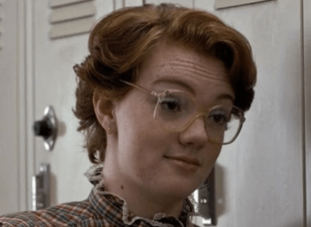 Barb standing in front of a hallways full of lockers.