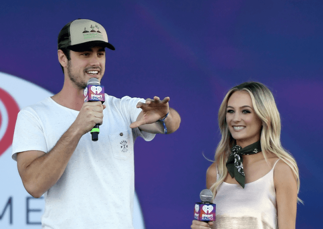 Ben Higgins and Lauren Bushnell standing next to each other as they hold microphones.