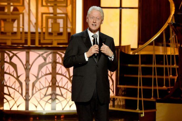 Bill Clinton stands while holding and talking into a microphone.
