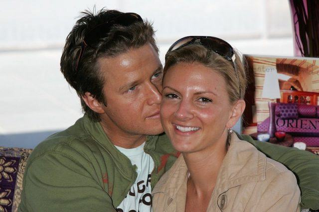 Billy Bush and Sydney Davis sit on a couch together.