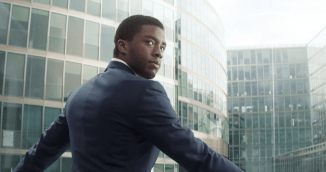 T'Challa standing in front of buildings and turning his head back.