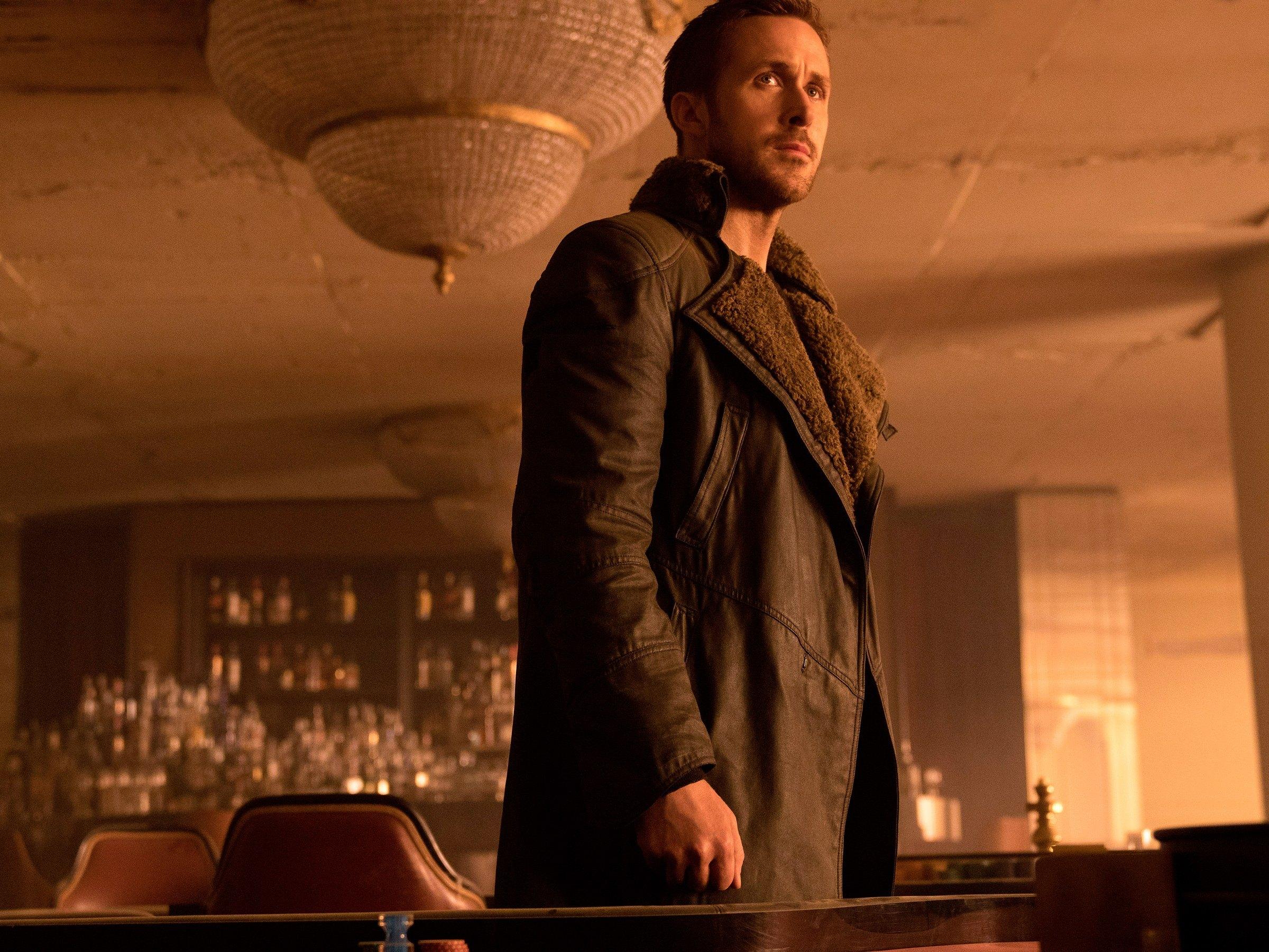 Ryan Gosling stands in a restaurant under a chandelier in Blade Runner 2049