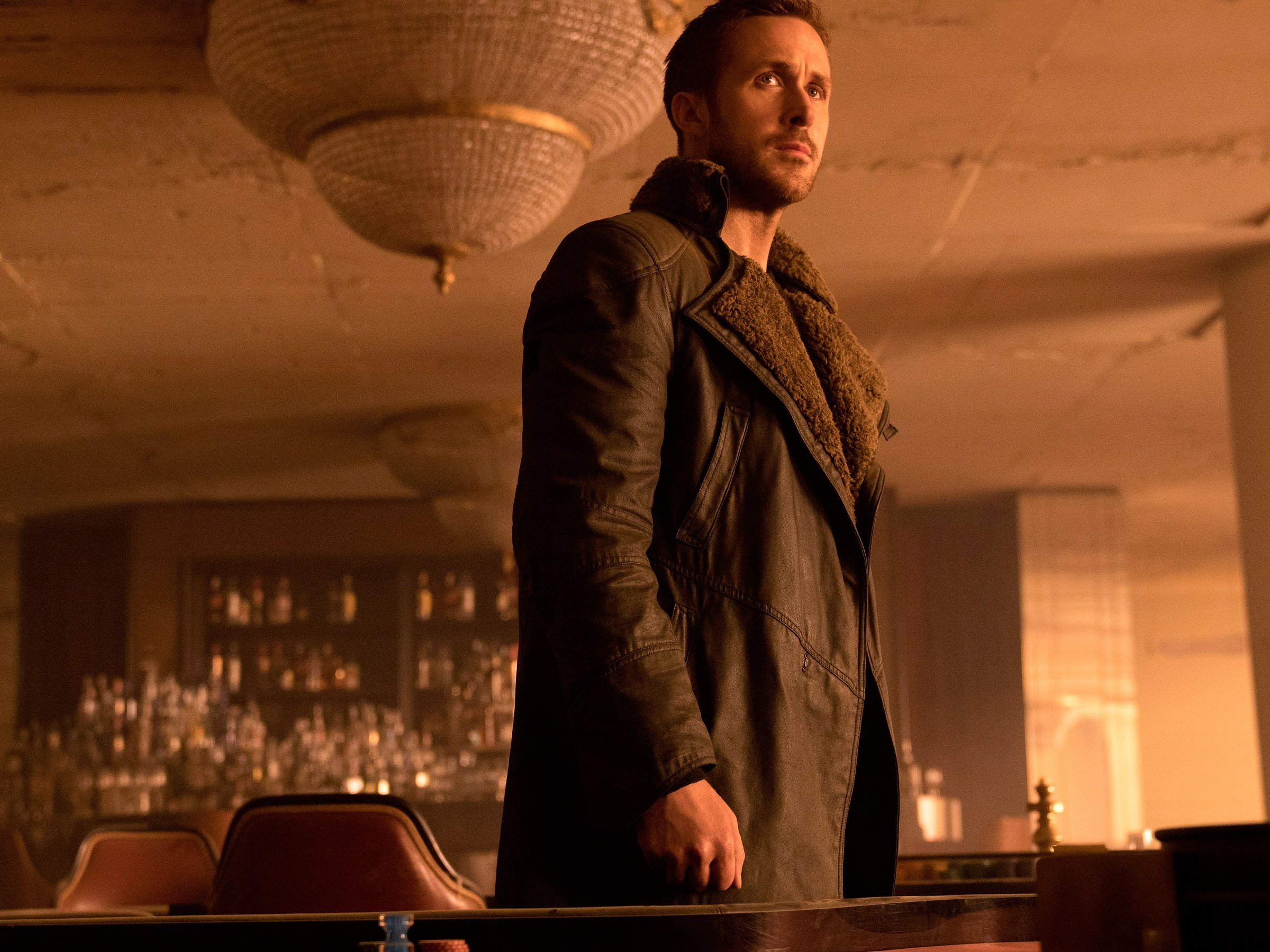 Ryan Gosling stands in a restaurant under a chandelier in Blade Runner 2049