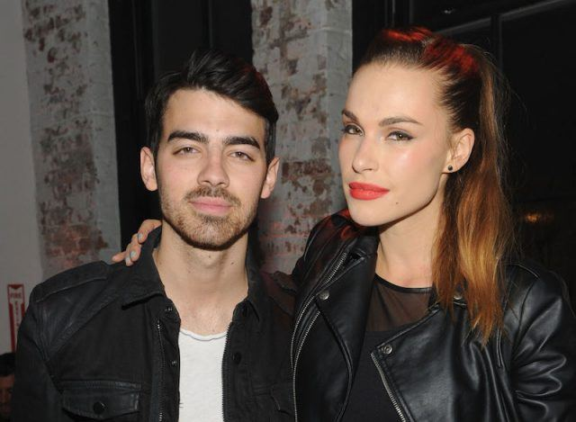 Blanda Eggenschwiler and Joe Jonas posing together at a fashion event.