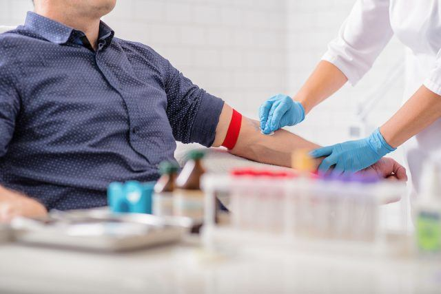 A doctor preps a patient before a blood donation.