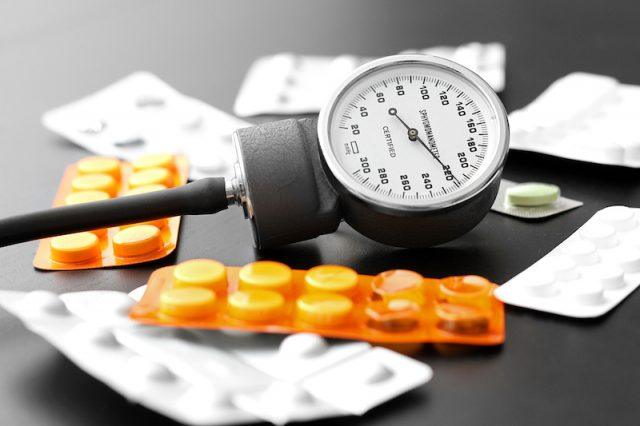 Blood pressure medication and tools on a black table.