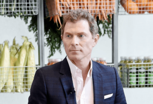 Bobby Flay standing in a plaid dark suit in front of baskets of vegetables and products.