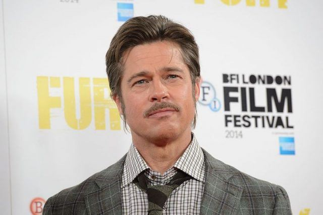 Brad Pitt stands on the red carpet of a movie premiere.