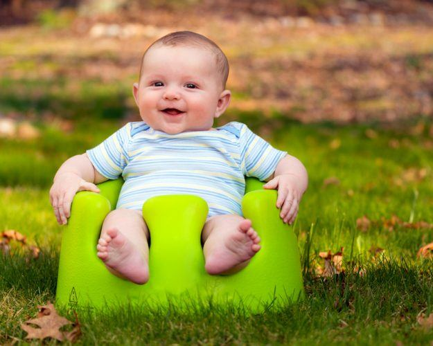 A baby sits on a bright green bumbo seat.
