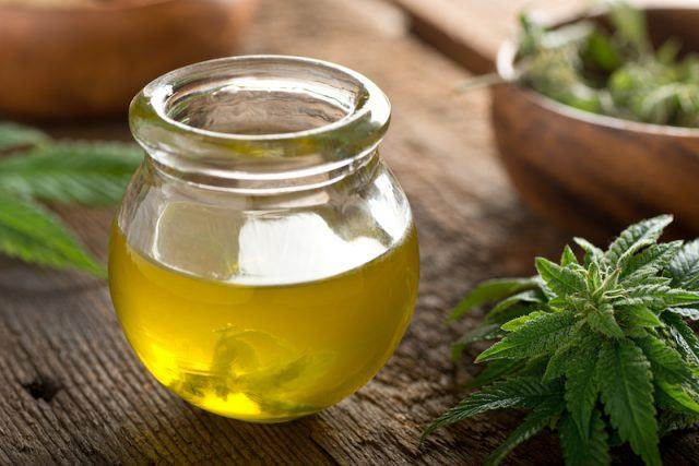 A clear jar filled with CBD Oil on a wooden table.