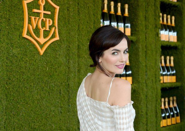 Camilla Belle looks over her shoulder while attending a champagne event.