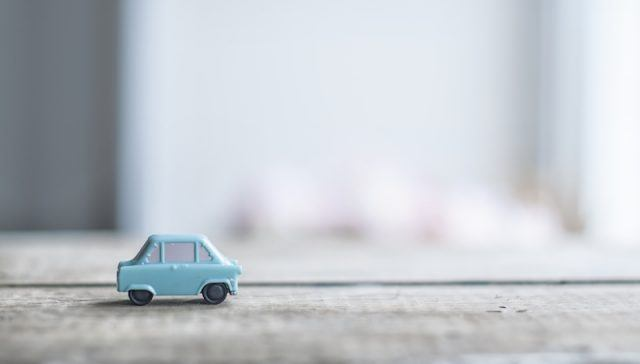 A small toy car on a carpet.