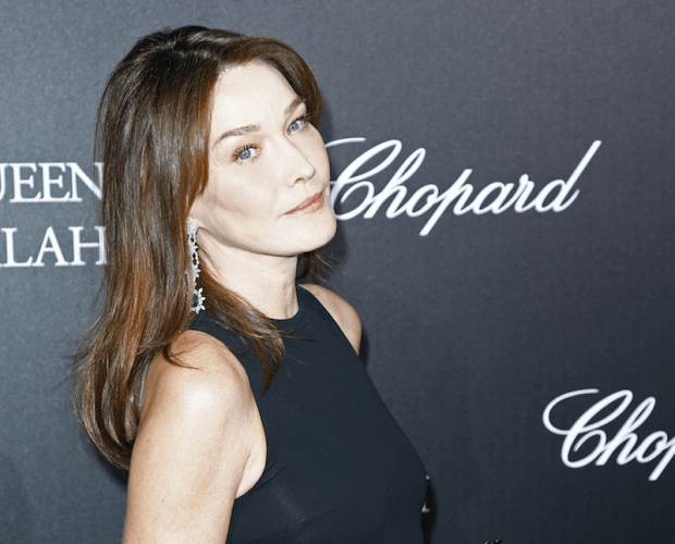Carla Bruni poses at a red carpet in a black dress.