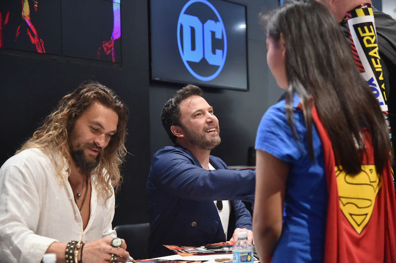 Jason Momoa sits next to Ben Affleck while talking to fans