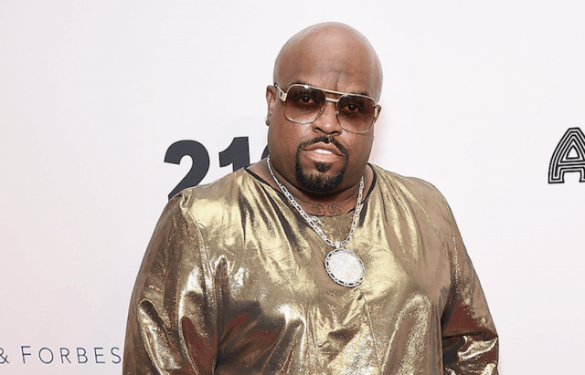 Cee Lo Green in gold shades and a gold shirt on a red carpet.