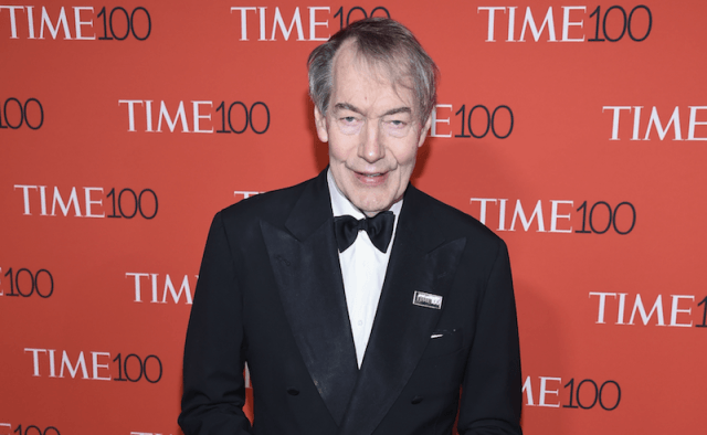 Charlie Rose stands and smiles in a black tuxedo while standing on a red carpet.