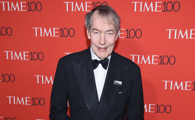 charlie rose in front of a time 100 screen in a tuxedo