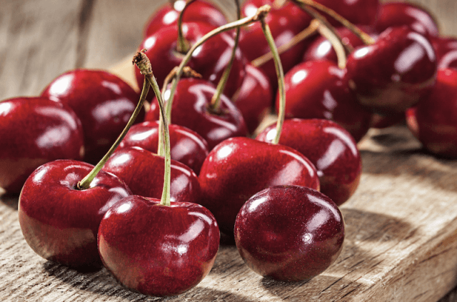 Cherries laid out on a wooden table.