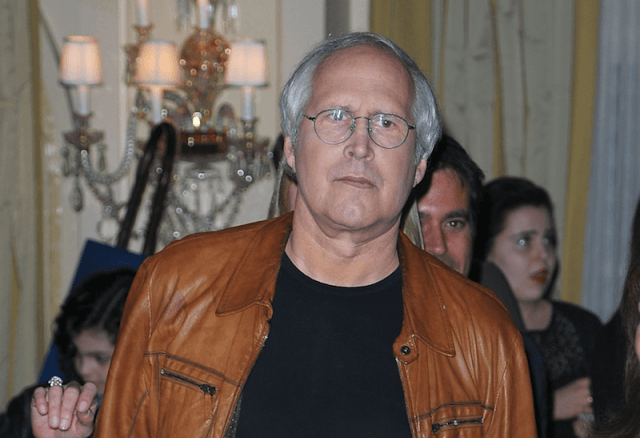 Chevy Chase in a tan leather jacket looking straight ahead.
