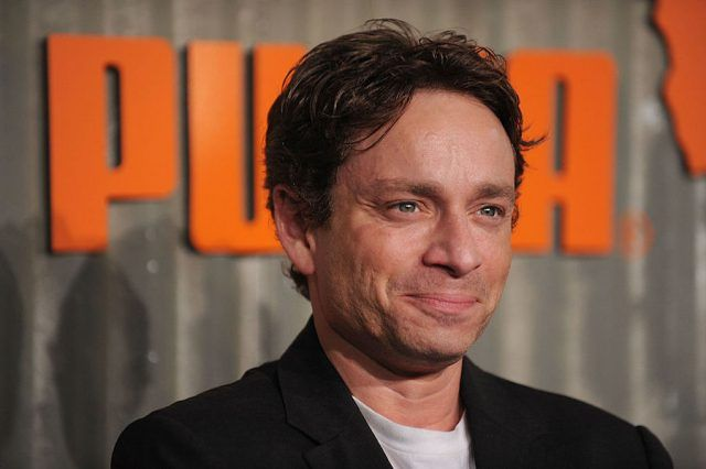Chris Kattan smiles and looks straight ahead as he stands at a Puma event.