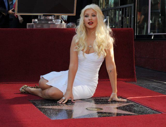 Christina Aguilera posing with her star in a white dress.
