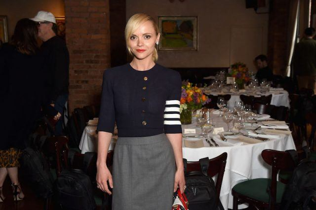 Christina Ricci standing in front of formal dinner tables.