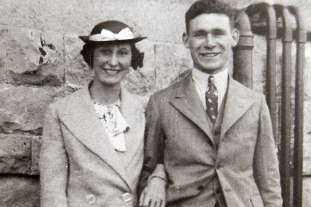 Clifford and Marjorie Hartland posing together in front of a building.