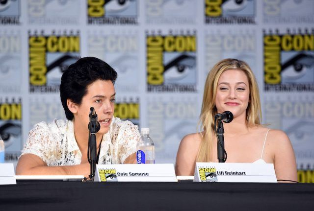 Cole Sprouse and Lili Reinhart sit next to each other in front of microphones while at a Comic-Con panel.