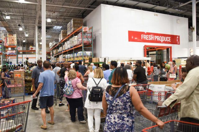 A crowd of shoppers pushing carts and products at a Costco location.