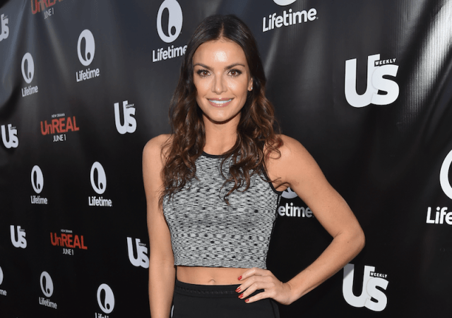 Courtney Robertson poses with one hand on her hip while on a red carpet.