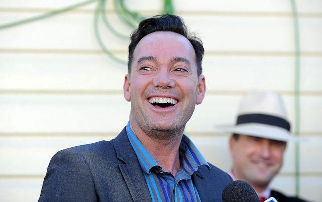Craig Revel Horwood smiling while standing in front of a microphone podium.