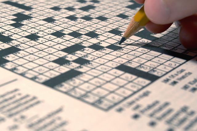 A person does a crossword puzzle with a pencil.