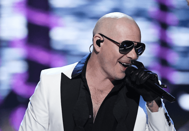 Pitbull holding a microphone and performing at a concert.