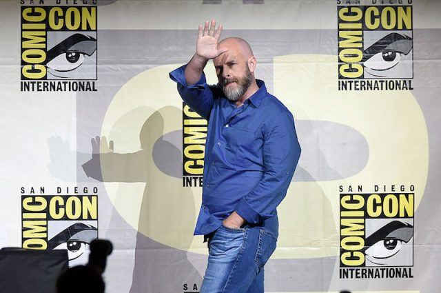 Dave Erickson waving to the crowd while walking across the stage at Comic Con.