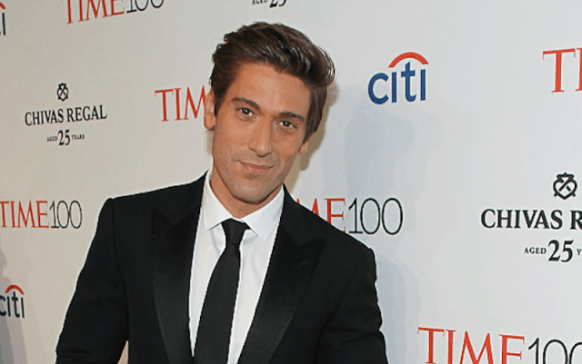 David Muir stands in a black suit and tie while posing for photos on the red carpet.