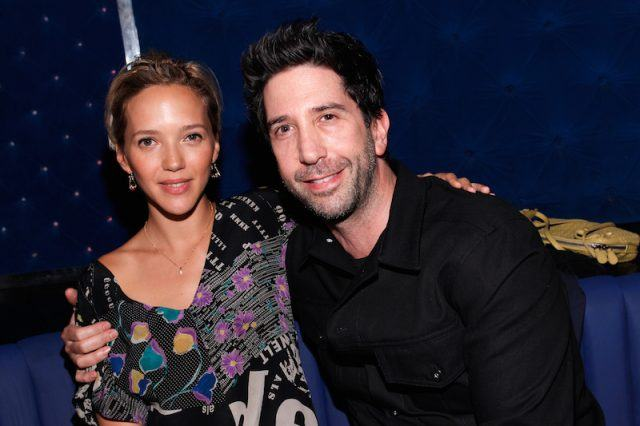 David Schwimmer and Zoe Buckman sit together on a couch.