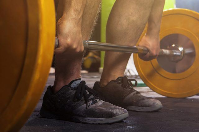 A person picking up weight equipment.