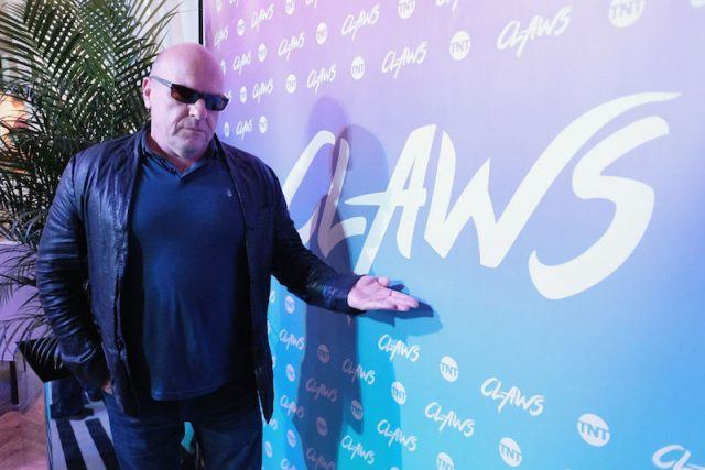Dean Norris pointing at a sign at a red carpet event while wearing shades and a leather jacket.
