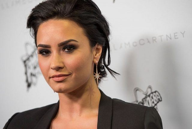 Singer Demi Lovato poses on a red carpet wearing gold earrings and a black blazer.