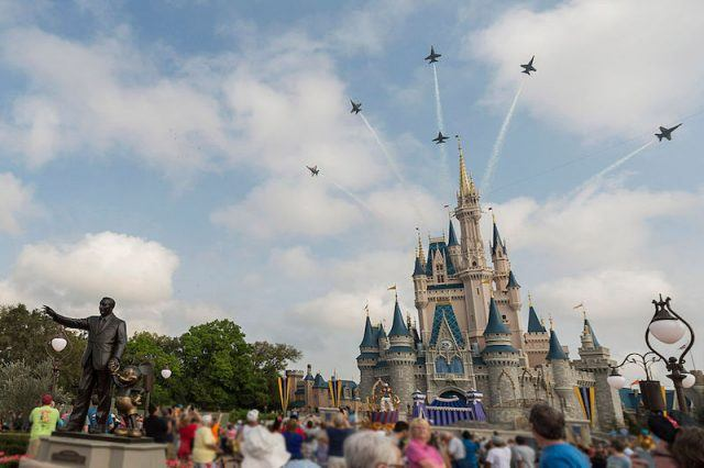 Disneyland castle seen with jet planes in the sky.