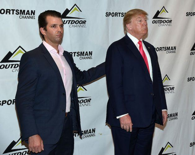 Donald Trump Jr stands next to Donald Trump while posing for photographers.