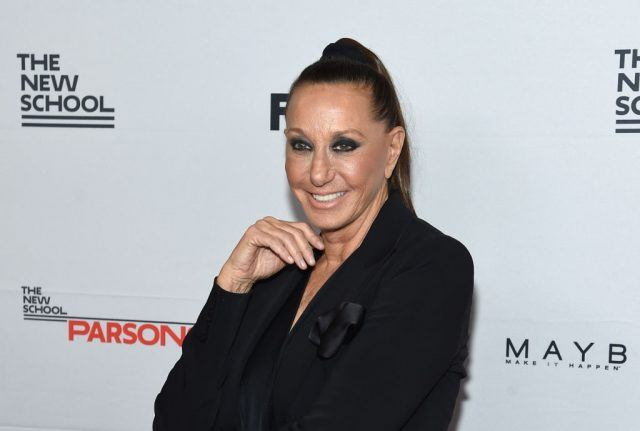 Designer Donna Karan smiles while holding up her hand at a fashion event.