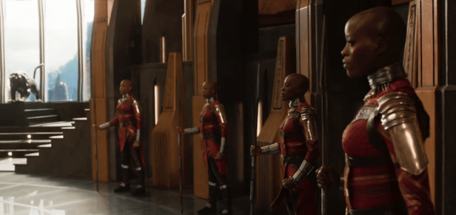 Bodyguards dressed in red standing outside of rooms.