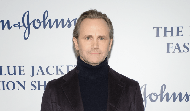 Lee Tergesen standing in a black turtleneck and dark jacket and staring straight ahead.